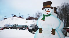 Plywood snowman, cableway and car parking at winter day Stock Footage