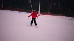 Back of girl in red down on slope at winter on hill of sports complex Stock Footage