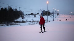 Woman in red down on slope at winter on hill of sports complex Stock Footage