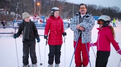 Family of four skiers pose at winter evening at track in ski resort Stock Footage