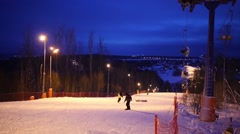 Snowboarders and funicular at night in skiing sports complex Stock Footage