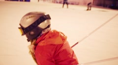 Girl child skier in helmet quickly down on slope at night Stock Footage