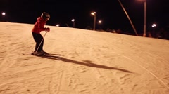 Girl child skier in helmet slowly down on slope at night Stock Footage