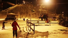 People move on funicular at night and skiers in ski resort Stock Footage