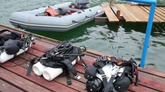 Aqualungs for diving on wooden pier and inflatable boat on river Stock Footage