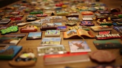 Refrigerator souvenir magnets on wooden floor Stock Footage