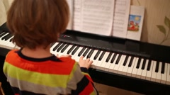 Back of boy playing on synthesizer and looking at sheets with notes Stock Footage
