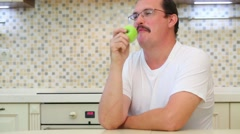 Man with glasses and white t-shirt eating green apple Stock Footage