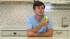 Man with glasses and blue t-shirt eating green apple Stock Footage