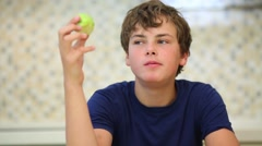 Close-up boy in dark blue shirt eating green apple Stock Footage