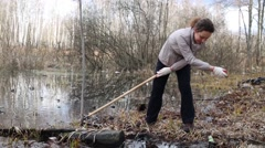 Woman pulls out garbage from water during cleaning of territory Stock Footage