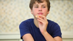 Happy boy teen eats fresh orange tangerine in kitchen Stock Footage