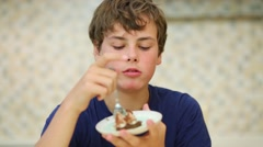 Happy boy teen eats confection from saucer in kitchen Stock Footage