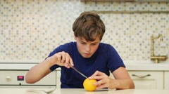 Happy boy teenager cleans orange with knife in kitchen Stock Footage