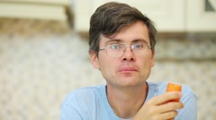 Man in glasses and blue t-shirt eats fresh carrot in kitchen Stock Footage