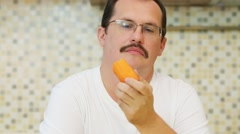 Man in glasses and white t-shirt eats fresh carrot in kitchen Stock Footage