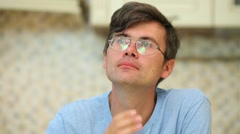 Man corrects his glasses and hair in kitchen. Shallow dof Stock Footage