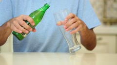 Close-up of man in blue t-shirt poured beer into glass Stock Footage