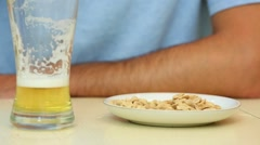 Hands of man drinking beer and eating peanuts on table Stock Footage