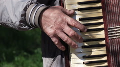 Old man plays on old accordion - stock footage