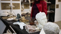 Woman came to desktop of sculptor with plaster head Stock Footage