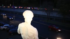 Plaster copy of statue of David by Michelangelo and cars go on road Stock Footage