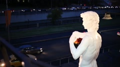 Copy of statue of David by Michelangelo and cars go on road Stock Footage