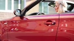 Blonde young woman sits in red sport car and opens door at summer day Stock Footage