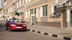 Red cabriolet car moves on asphalt near building at summer Stock Footage