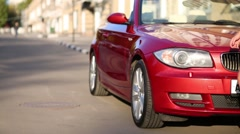 Legs of woman going near red cabriolet car at summer Stock Footage