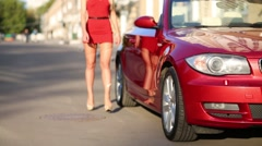 Legs of woman in red going near red cabriolet car at summer Stock Footage