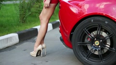 Legs of woman in red posing near red car at summer Stock Footage