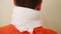 Back of boy teenager with gauze bandaged on neck in room Stock Footage
