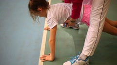 Teacher helps for girl to make press-up exercise. Top view Stock Footage