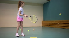 Girl in shorts learns to hold racket and beat off balls Stock Footage