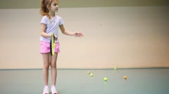 Girl in shorts learns to hold tennis racket and beat off balls Stock Footage