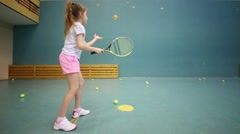 Back of girl in shorts learning to beat off balls from wall Stock Footage