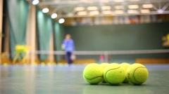 Yellow balls for tennis and training people out of focus Stock Footage