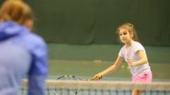 Girl learns to beat off balls over net during tennis training. Stock Footage