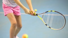 Girl beats off ball during tennis training in sport hall Stock Footage