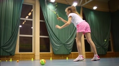 Girl learns to beat off balls during tennis training Stock Footage