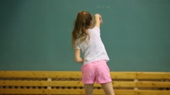 Back of girl throwing tennis balls during training Stock Footage