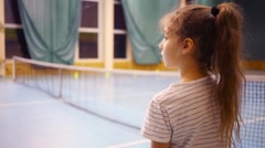 Back of girl and tennis net with players out of focus Stock Footage