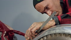 Bike mechanic checking out a motorbike while fitting a mud guard. - stock footage