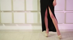 Close-up of legs in shoes of woman in dress standing near wall Stock Footage