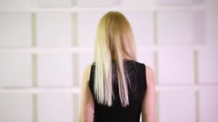 Back of unidentified blonde woman in black dress going away - stock footage