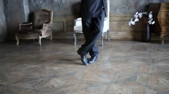 Legs of man in black suit and hat dancing tango in retro room Stock Footage