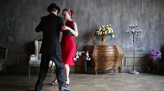 Woman in red dress and man in black suit dance tango Stock Footage
