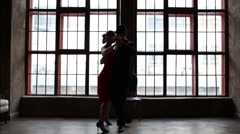 Woman in red dress and man in black suit dance tango near window Stock Footage