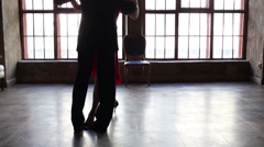 Legs of woman in red and man in black dancing tango near window Stock Footage